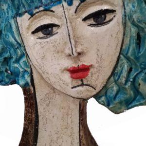 dettaglio scultura volto di donne con capelli turchini