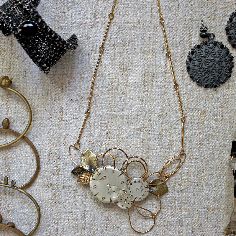 collana con vecchio orologio, bracciale nero e bracciali in ottone