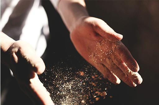 mani che si battono per levare la polvere