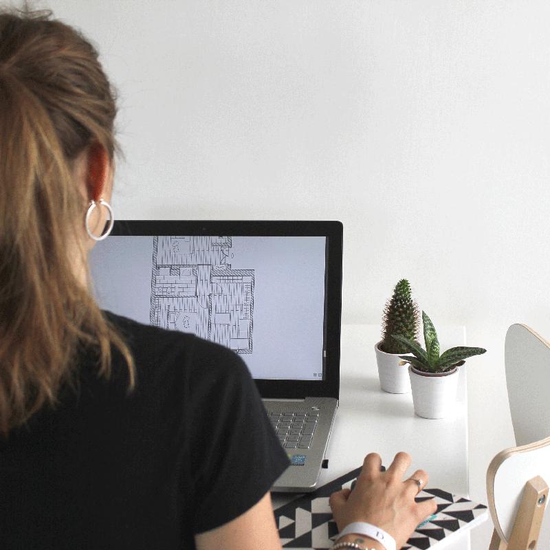 Ragazza con coda di spalle lavoraad un progetto al computer