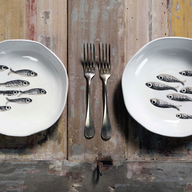 piatti bianchi con disegni di pesci grigi e forchette su tavolo in legno