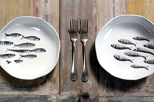 tavolo in legno vintage con due piatti pitturati a mano raffiguranti sardine e due forchette