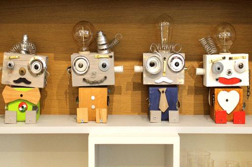 robot fatti in legno poggiati su una libreria di legno