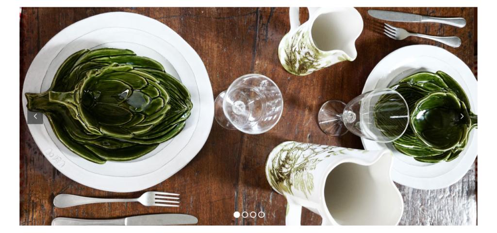tavola apparecchiata con vassoi in ceramica bianchi e verdi con motivi floreali e foglie